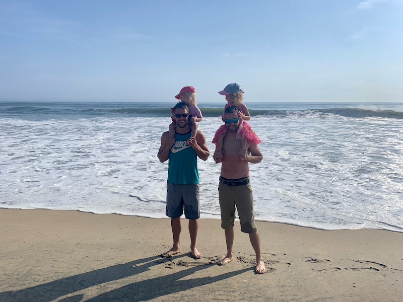 Fathers with toddler daughters on their shoulders at the beach in Outer Banks, NC.