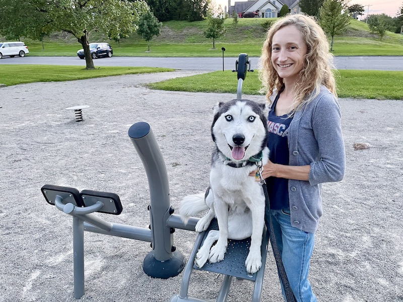 Girl standing with husky at park