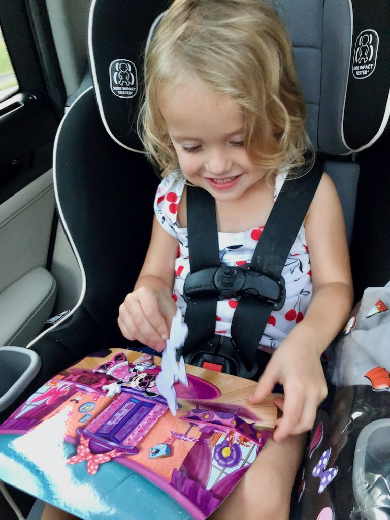 Toddler playing with Minnie Mouse puffy sticker playset in carseat.