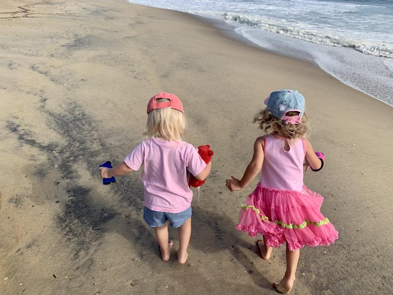 Toddler girls walking on beach in Kill Devil Hills, NC