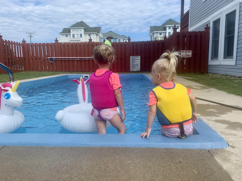 Toddler girls sitting by pool with life jackets on.