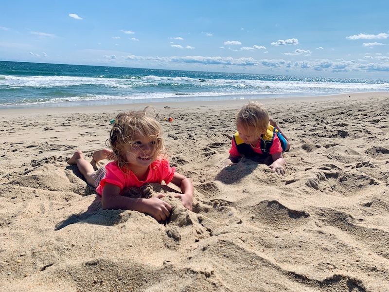 Toddler girls on the beach laying in the sand in the Outer Banks