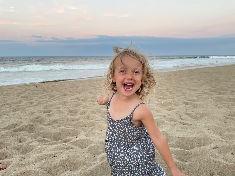 Toddler girl laughing at the beach in Kill Devil Hills, NC