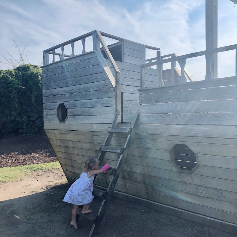 Toddler girl climbing pirate ship at Outer Banks Brewing Station in Outer Banks