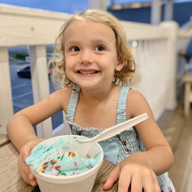 Toddler girl eating ice cream at Jockey's Ridge State Park.
