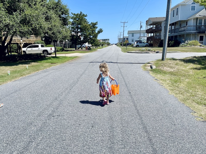 Toddler girl holding sand pail while walking to the beach in Outer Banks.