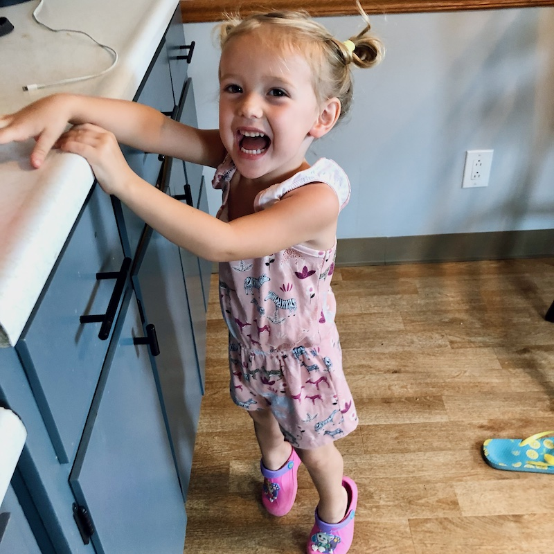 Toddler standing on tippy toes trying to reach countertop