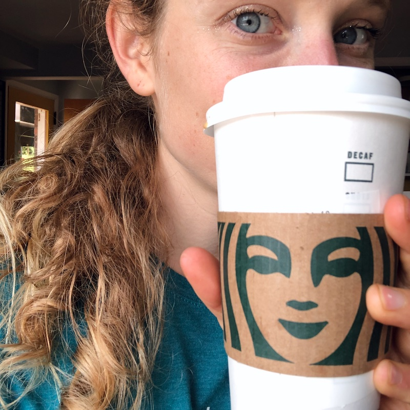 Girl holding Starbucks to go coffee cup