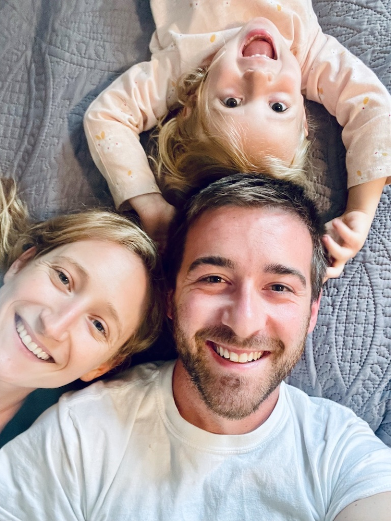 Mom and dad with daughter laying on bed smiling for selfie
