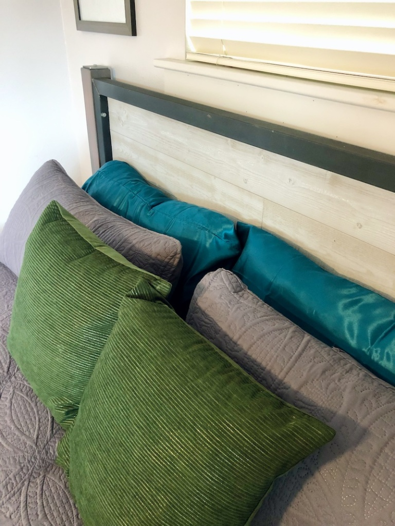 Green, gray, and teal pillows on king sized bed with homemade steel and wood headboard
