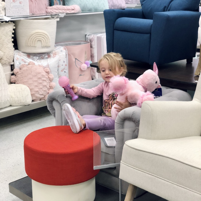 Toddler girl sitting on couch in TJMaxx