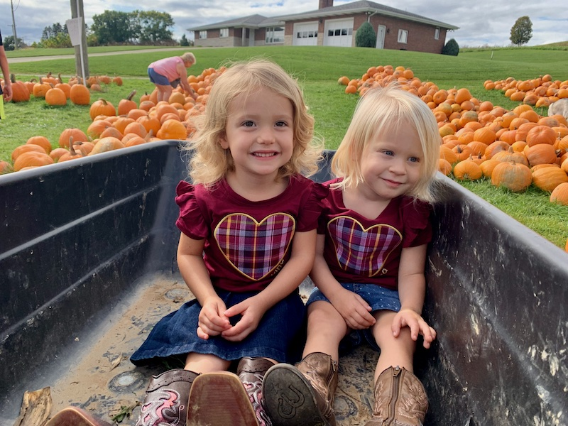 Toddler girls in matching outfits at pumpkin patch