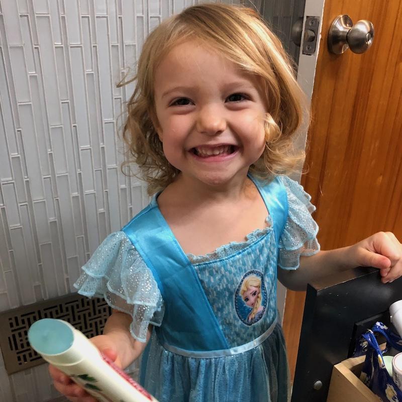 Toddler using deodorant as lip gloss
