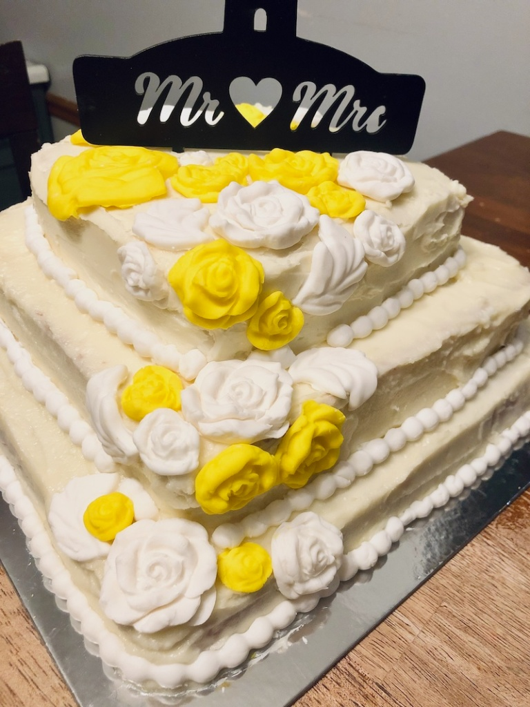 Three layer wedding cake with white and yellow roses